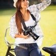 Casual young woman with camera outdoors — Stok fotoğraf