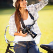 Casual young woman with camera outdoors — ストック写真