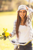 Cheerful young woman in a bicycle outdoor — Stock Photo