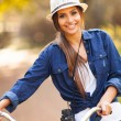 Pretty woman with bike and binoculars at park — Stock Photo #26390373