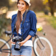 Stock Photo: Young girl posing with her photo camera