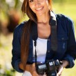 Pretty woman with a camera outdoors — ストック写真