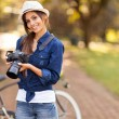 Young female photographer with camera outdoors — Stock Photo