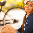 Young fashion model sitting outdoors — Stock Photo