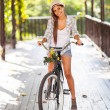 Young woman riding bike outdoors — Stock Photo