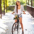 Young woman riding bike outdoors — Stock Photo #26392725