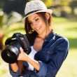 Young female photographer checking pictures on camera — Stock Photo