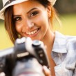 Beautiful young woman holding camera outdoors — Stock Photo