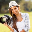 Attractive girl holding camera outdoors — Stok fotoğraf