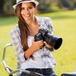 Happy young woman holding camera outdoors — Stock Photo