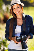 Pretty woman with a camera outdoors — Stok fotoğraf