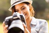 Pretty woman reviewing photos on camera — Stock Photo