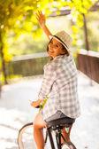 Young woman riding her bike waving goodbye — Стоковое фото