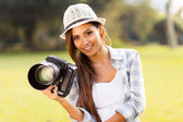 Attractive girl holding camera outdoors — Stock Photo