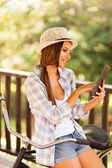 Mladá žena, čtení e-mailů v tabletovém počítači venku — Stock fotografie