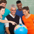 High school students and teacher looking at globe — Stock Photo #26791207