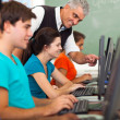 Middle aged teacher teaching computer to students — Stock Photo