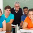Middle aged high school teacher with group of students — Stock Photo #26794699