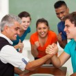 Middle aged teacher arm wrestling with high school student — Stock Photo #26795157