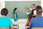 Teacher pointing at chalkboard with student standing in front of — Stock fotografie