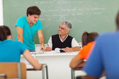 Senior high school educator helping student — Stock Photo