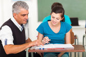 Mature high school teacher helping student — Stock Photo