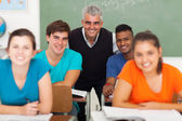 Middle aged high school teacher with group of students — Stock Photo