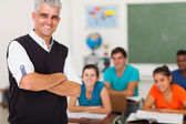 Middle aged teacher standing in front of the class — Stock Photo