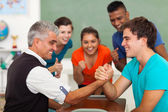 Middle aged teacher arm wrestling with high school student — Stock Photo
