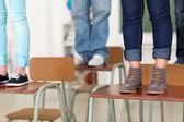Teen students standing on school desks — Stock Photo