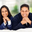 Happy indian couple lying on bed — Stock Photo #26800353