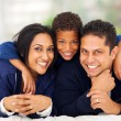 Stock Photo: Little indian boy hugging his parents on bed