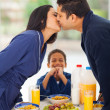 Stock Photo: Little boy is laughing when seeing parents kissing before breakf