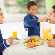 Little boy feeding his father fruit - Stock Photo