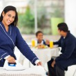 Indian woman ironing while husband and son having breakfast — Stock Photo