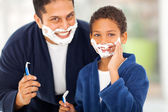 Son playing with father's shaving foam — Stock Photo