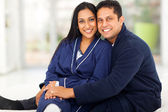 Loving indian couple sitting in bedroom — Stock Photo