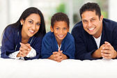 Indian family lying on bed together — Stock Photo