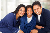 Cute indian family sitting on bed — Stock Photo
