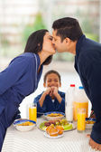 Little boy is laughing when seeing parents kissing before breakf — Stock Photo