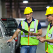Shipping company workers inspecting vehicle — Stock Photo #27014363