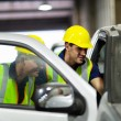 Stock Photo: Warehouse workers inspecting vehicle