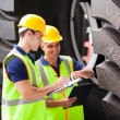 Stock Photo: Shipping workers at harbor inspecting tires