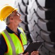 Warehouse worker inspecting tires — Stock Photo