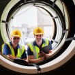 Warehouse workers standing between industrial tires — Stock Photo