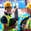 Young harbor workers pointing the forklift — Stock Photo