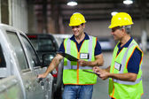 Shipping company workers inspecting vehicle — Foto Stock