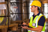 Shipping company worker recording steel rolls — Stock Photo