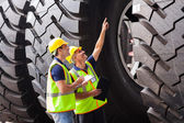 Shipping company workers checking industrial tires — Stock Photo