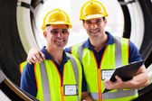 Shipping company inspectors standing in between industrial tires — Stock Photo